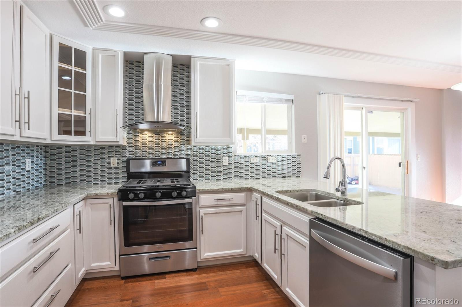 Stunning Kitchen with Granite Counters, Tons of Cabinets and Custom Stainless Range Hood Over a 5-Burner Gas Range