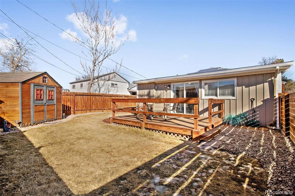 Fenced yard with deck and storage shed.